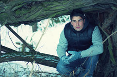 Crouching handsome young man in winter Stock Images