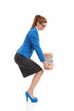 Crouching with heavy stack of books Royalty Free Stock Photography