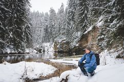 A crouching hiker by the winter river. With steep banks and snowy forest Stock Photography