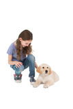 Crouching little girl next dog. On white background Stock Photos