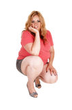 A crouching plus size woman. A plus size pretty woman in shorts crouching in the floor, holding her Stock Image