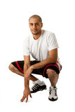 Crouching Sporty guy. Sporty handsome African Hispanic guy crouching and hand on floor, isolated Royalty Free Stock Photos