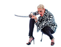 Crouching woman. A crouching beautiful young woman yells out as she prepares to thrust her sword into her attacker while isolated on a white background Stock Photos