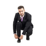 Crouching young businessman tying shoe laces looking at camera. Full body length portrait isolated over white studio background Stock Photography