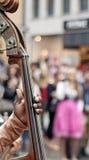 Croud des personnes entendant un joueur de violoncelle Photographie stock
