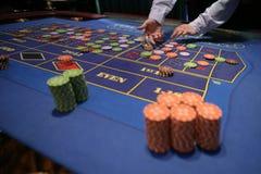 Crouoier atrás da tabela de jogo em um casino Fotos de Stock Royalty Free