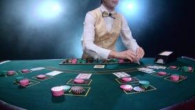 Crouoier que coloca cartões para o pôquer na tabela no casino Fumo Movimento lento video estoque