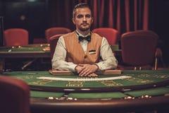 Croupier bak dobbleritabellen i en kasino arkivbild