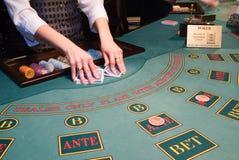 Croupier battant des cartes de jeu à la table de tisonnier Images stock