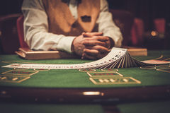 Croupier behind gambling table in a casino Royalty Free Stock Image