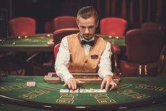 Croupier behind gambling table in a casino Stock Photo
