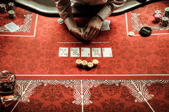 Croupier dealing card at poker table in casino. Partial view of croupier dealing card at poker table in casino Royalty Free Stock Image