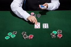 Croupier dealing cards. In a poker game placing them face up on the green baize of the gaming table royalty free stock images