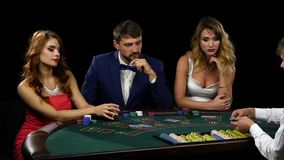 Croupier deals the card three players sitting at the table stock video