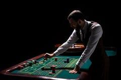Croupier derrière la table de jeu dans un casino Image stock