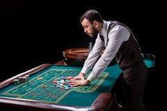 Croupier derrière la table de jeu dans un casino Images stock