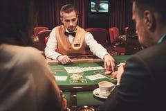 Croupier derrière la table de jeu dans un casino Photos stock