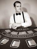 Croupier handlar kort på den modiga blackjacktabellen royaltyfri foto