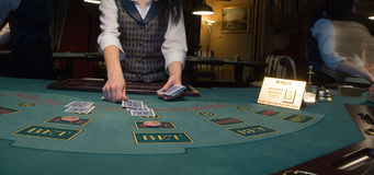 Croupier handling cards at poker table Royalty Free Stock Photo
