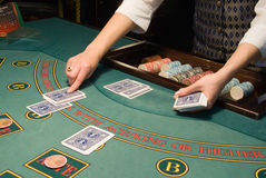 Croupier handling cards at poker table Stock Image