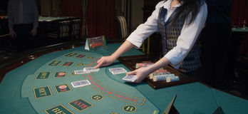 Croupier handling cards at poker table Stock Photos
