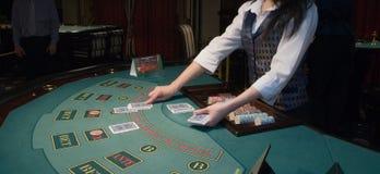 Croupier handling cards at poker table stock photos