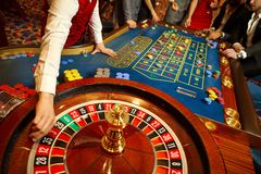 The croupier holds a roulette ball in a casino in his hand. Gambling in a casino royalty free stock images