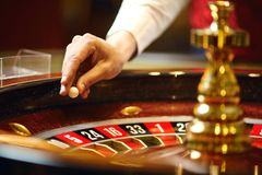The croupier holds a roulette ball in a casino in his hand. Gambling in a casino stock image