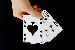 Croupier player holding card aces four of a kind. Croupier player holding in hand card ace of spades four of a kind on black background Stock Photography