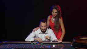 Croupier pushes a young couple to win at roulette chips stock video