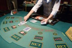 Croupier que segura cartões na tabela do póquer Fotografia de Stock