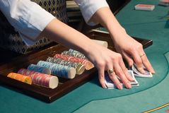 Croupier shuffling cards at poker table Royalty Free Stock Photo