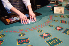 Croupier shuffling playing cards at poker table. Dealer shuffling playing cards at a poker table in casino Stock Images