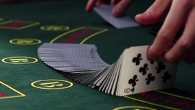 Croupier shuffling poker playing cards on green table, slow motion stock video