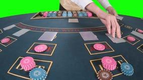 Croupier som behandlar professionellt spela kort på en pokertabell, satte tre kort är misslyckandet framme av honom Gräsplan arkivfilmer