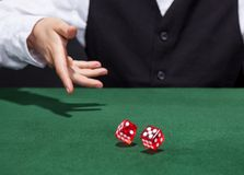 Croupier throwing a pair of dice. Croupier throwing a pair of red dice across the green felt on a card table in a casino in a game of chance Stock Images