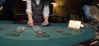 Croupier traitant des cartes à la table de tisonnier Photo libre de droits