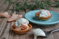 Croustades with salmon and dill weed mayonnaise. Two croustades on a wooden board with a blue plate Stock Image