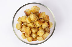 Croutons. Small portion of croutons in the little glass bowl over grey background stock photos
