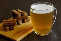 Croutons with beer. Croutons of bread with beer with wooden place royalty free stock photography
