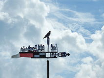 Crow bird on weather vane. Crow bird on beautiful weather vane in cloudy sky background, Lithuania stock photography