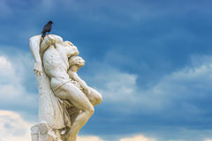 Crow on statue The Spartacus Oath in the Tuileries Gardens in Pa royalty free stock photography
