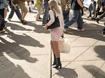 In The Crowd. A woman passes through a busy sidewalk after an afternoon of shopping stock photo