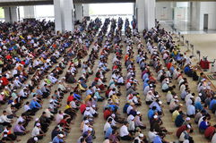 Crowd. Sitting in horizontal lines for a prayer in the Stock Photo