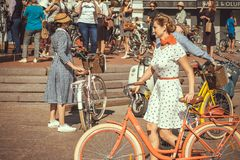 Crowd of active people with cycles in bright vintage clothing at cosplay festival in Europe Royalty Free Stock Photography