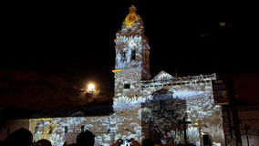 Crowd admiring the spectacle of lights projected on the facade of the Church of Santo Domingo, in the historical center of Quito. Royalty Free Stock Images