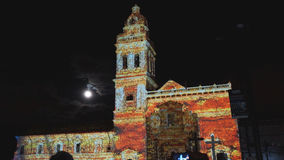 Crowd admiring the spectacle of lights projected on the facade of the Church of Santo Domingo, in the historical center of Quito. Stock Photography