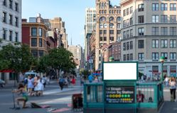 Crowd of anonymous people walking around a blank billboard sign. In Union Square Park near the 14th street subway station in Manhattan, New York City NYC stock images