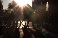 Crowd of anonymous people walking on sunset in the city streets silhouettes stock image