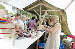 Crowd at an arts and crafts market. A crowd of people at an outdoor arts and crafts market looking at colorful crafts and jewelry stock photo